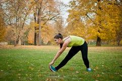 Женщина выполняет протягивать перед jogging Стоковое Изображение RF