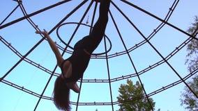 Женщина выполняет фокусы на кольце для акробатики, закручивая в воздухе сток-видео