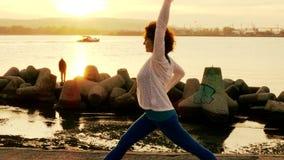 Женщина выполняя тренировки йоги на пляже