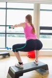 Женщина выполняя тренировку аэробики шага с гантелями Стоковое фото RF
