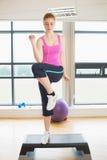 Женщина выполняя тренировку аэробики шага Стоковые Фотографии RF