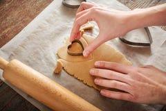 Женщина высекает печенья имбиря в форме сердец с металлом s Стоковое Изображение RF