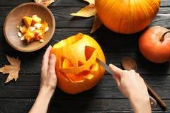 Женщина высекая фонарик jack головы тыквы хеллоуина на деревянном столе стоковые фотографии rf