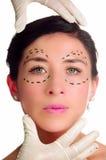 Женщина выстрела в голову кавказская при пунктирные линии нарисованные вокруг глаз смотря в камеру, докторов вручает держать ее г Стоковые Изображения