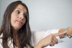 Женщина выстукивая на наручных часах стоковое изображение
