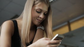 Женщина вытаращится в телефоне и усмехаться во время пролома между разминкой сток-видео