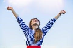 Женщина вытягивает руки к солнечному свету против неба Стоковое Фото