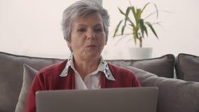 Женщина выхода на пенсию наслаждаясь сообщением и используя ноутбук сток-видео