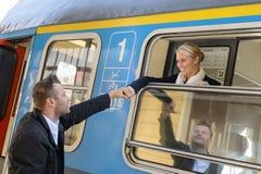 Женщина выходя при человек поезда держа руку стоковые фото