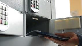 Женщина выходя мобильный телефон в шкафчик для поручать видеоматериал