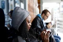 Женщина вьющиеся волосы в сером клобуке используя телефон Стоковые Фото