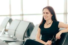 Женщина в авиапорте заявляя зал ожидания сидя на стуле стоковое фото rf