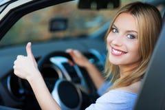 Женщина в автомобиле давая большие пальцы руки вверх