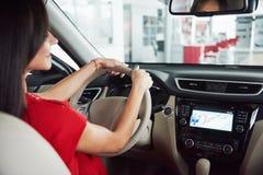 Женщина в автомобиле крытом держит колесо повернуть вокруг усмехаясь смотря пассажиров в водителе такси идеи заднего сиденья прот стоковое фото rf