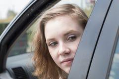 Женщина в автомобиле смотрит вне окно назад осматривает стоковое фото rf