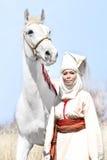 Женщина в азиатском белом национальном платье с белой лошадью в природе Стоковое фото RF