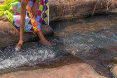 Женщина в африканском обмундировании на краю беглого реки Interactin Стоковые Изображения