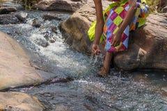 Женщина в африканском обмундировании на краю беглого реки Interactin Стоковое Фото