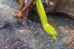 Женщина в африканском обмундировании на краю беглого реки Interactin Стоковая Фотография
