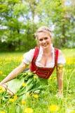 Женщина в баварских одеждах или dirndl на лужке Стоковые Фотографии RF