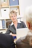 Женщина в банке говоря к клиентам стоковое фото