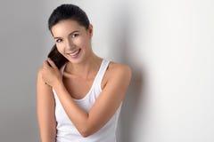 Женщина в безрукавной блузке регулируя волосы стоковое изображение