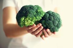 Женщина в белой футболке держа брокколи в руках скопируйте космос Здоровая чистая концепция еды вытрезвителя Вегетарианец, vegan, Стоковая Фотография