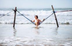 Женщина в белом купальнике сидит в качании гамака над wav океана Стоковые Изображения RF
