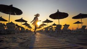 Женщина в белых платье и шляпе на восходе солнца на пляже Стоковое Изображение RF