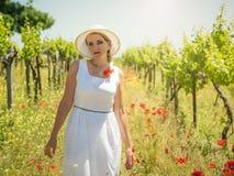 Женщина в белых платье и шляпе в рядах виноградины fields Стоковое фото RF