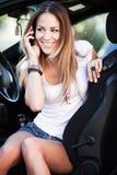 женщина в беседе автомобиля на сотовом телефоне Стоковые Изображения