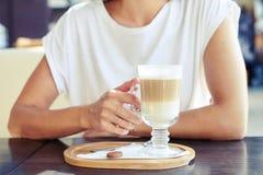Женщина в белой футболке держа чашку капучино стоковое фото rf