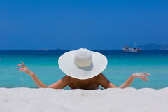 Женщина в белой шляпе лежа на пляже Стоковые Изображения