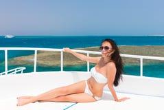 Женщина в белом купальнике лежа на палубе яхты на солнце Стоковая Фотография RF