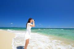 Женщина в белом платье смотрит на море стоковое изображение