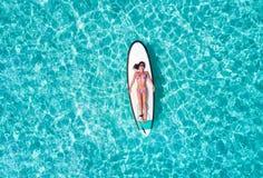 Женщина в бикини загорает на surfboard, стоковая фотография rf