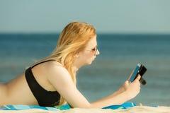 Женщина в бикини загорая и ослабляя на пляже Стоковое Фото