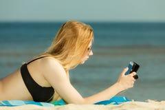 Женщина в бикини загорая и ослабляя на пляже стоковые фотографии rf