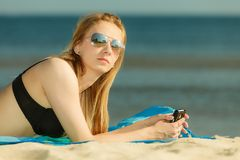 Женщина в бикини загорая и ослабляя на пляже стоковое фото rf