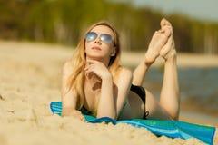 Женщина в бикини загорая и ослабляя на пляже стоковая фотография rf