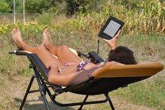 Женщина в бикини имеет остатки на шезлонге с электронной книгой Стоковая Фотография RF