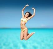 Женщина в бикини скача на пляж Стоковая Фотография RF