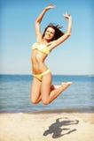 Женщина в бикини скача на пляж Стоковое фото RF