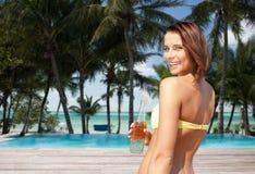 Женщина в бикини с бутылкой питья на пляже Стоковое Фото