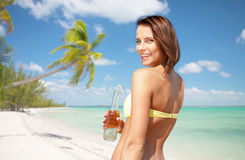 Женщина в бикини с бутылкой питья на пляже Стоковая Фотография