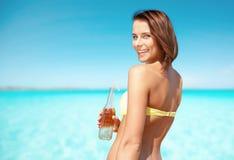 Женщина в бикини с бутылкой питья на пляже Стоковое фото RF