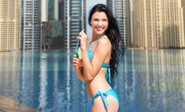 Женщина в бикини с бутылкой питья на пляже Стоковые Изображения RF