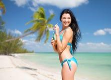 Женщина в бикини с бутылкой питья на пляже Стоковое Изображение
