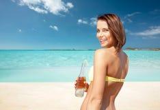 Женщина в бикини с бутылкой питья на пляже Стоковая Фотография RF