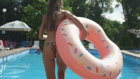 Женщина в бикини с раздувным кругом донута скачет в бассейн в замедленном движении акции видеоматериалы